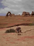 Delicate Arch with cairn in foreground.  They have to nail the rocks down up there!